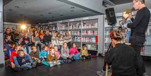 Foto van kindjes die kijken naar een poppentheater